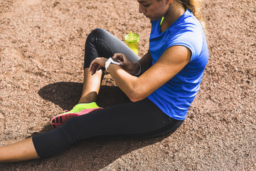 Sportive young woman sitting on sports field drinking looking at smartwatch