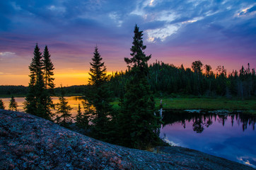 colorful sunrise with small lake reflecting in foreground