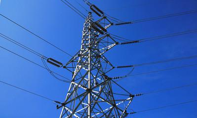 High voltage pole against blue sky.