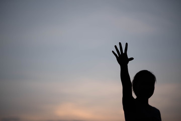 silhouette woman hand up at sunset
