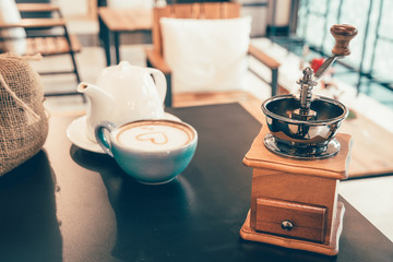 coffee grinder and hot cup of coffee