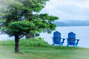 Blue cottage chairs facing the lake