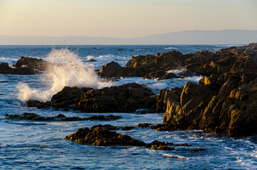 Wave crashing against rocks at sunset