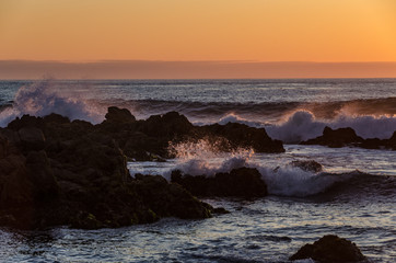 Multiple waves crashing on rocks at sunset