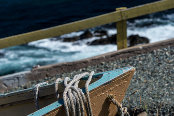 close up of old fishing boat bow with waves in the background