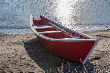 red fishing wooden dory on shoreline
