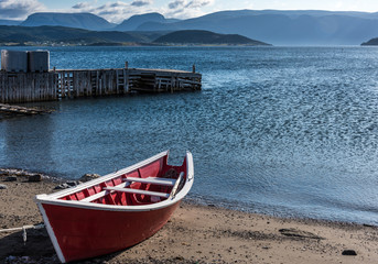 small wooden red fishing boat on shore