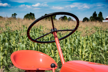 Close up of antique orange tractor with corn fields in background