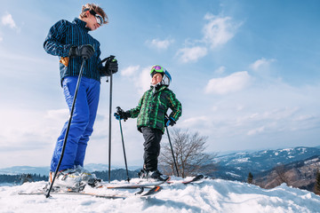Two skiers on the top of snow hill ready to slow down