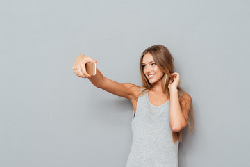 Smiling young girl making selfie photo isolated