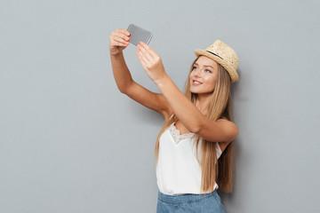 Smiling beautiful girl in hat making selfie photo on smartphone