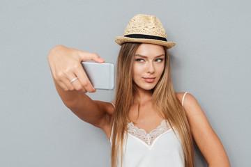 Portrait of beautiful girl in hat making selfie with smartphone
