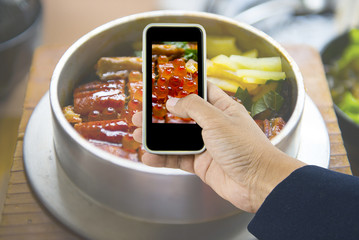 Man hands taking Japanese food photo by mobile phone...
