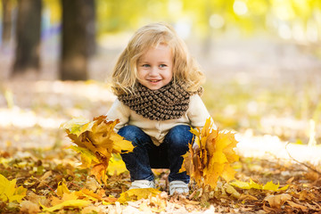 Joyful little girl in park in autumn with leaves in their hands