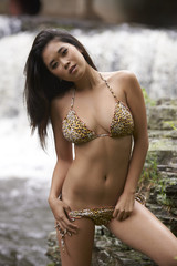Beautiful young Asian woman wearing bikini in front of rushing forrest waterfall on sunny day.
