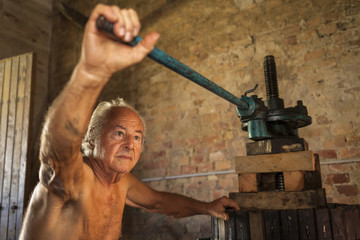 Old shirtless winemaker farmer working on a traditional wine press