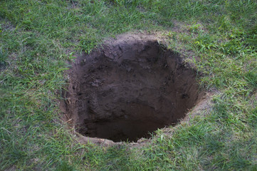 Deep dirt hole in ground or lawn