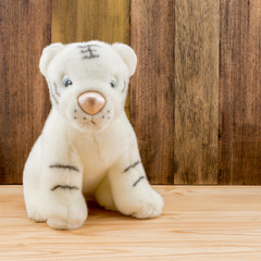 Plush liger doll toy for kid on wood background, The liger is a hybrid cross between a male lion and a female tiger.