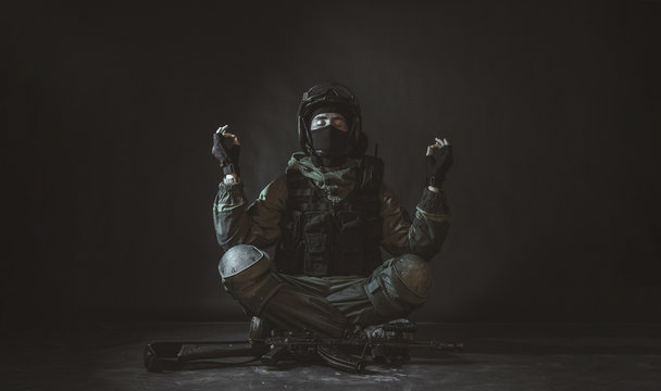 Young fitness member of special forces division meditation in dark room. Man is practicing yoga.Soldier knowing peace and harmony. Russian police special force - Special Rapid Response Unit (Spetsnaz)