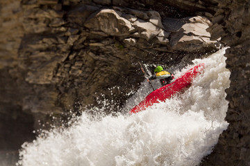 A male whitewater kayaker blasts through a waterfall on the Big Horn River, Nordegg, Alberta, Canada