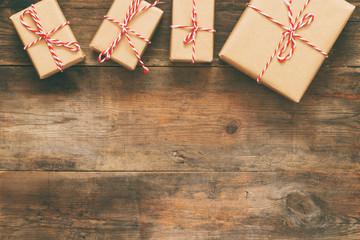 Flat lay image of handmade gift boxes over wooden background