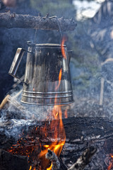 Kettle boiling over an open campfire in the forest