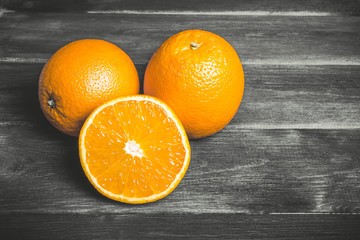 Orange cut into half, fruit section on black wooden table.