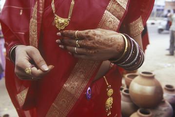 India, Rajsatan, Jaipur woman's hand with henna tattoo, red sari and gold jewellry
