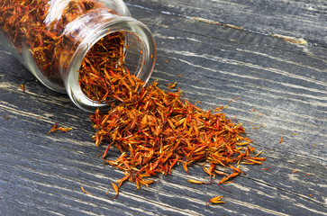 Saffron spice.Saffron in a glass bottle on a wooden background