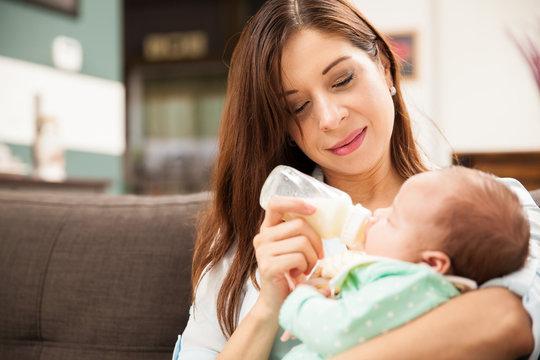 Cute mom feeding baby with formula
