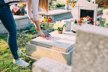 A woman cleans the grave. Fototapete