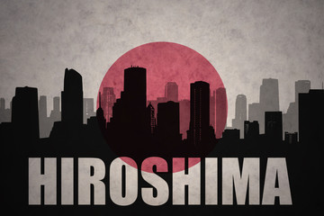 abstract silhouette of the city with text Hiroshima at the vintage japanese flag background