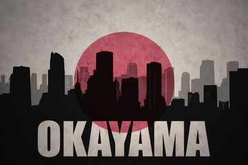 abstract silhouette of the city with text Okayama at the vintage japanese flag background