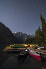 Canoes on Moraine Lake at night. Banff National Park, Alberta, Canada.