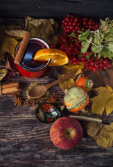 red cup of hot mulled wine in autumn among leaves