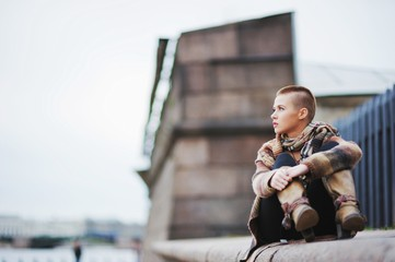 a beautiful short-haired girl sitting on the parapet with his le