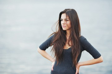 Beautiful long-haired woman peers into the distance on the shore of the Gulf of Finland, the wind ruffled her hair.
