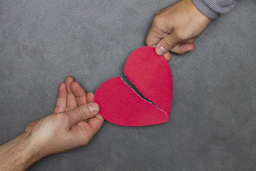 two people tearing paper red heart in half