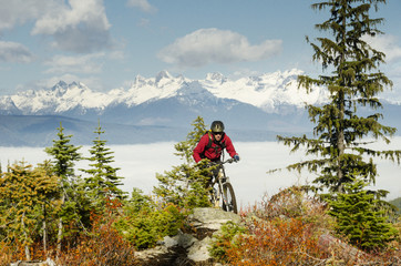 A mountain biker rides in front of the Valhalla Mountains on a trail called Vallelujah, Nelson, British Columbia