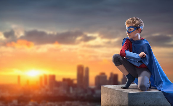 At sunset,little boy dressed as superhero watches over the city