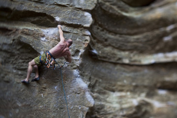 A strong male climber sport climbing RoShampo 12a, Red River Gorge, Kentucky Brown