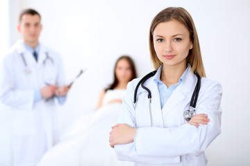 Friendly female doctor on the background with patient in the bed and his physician