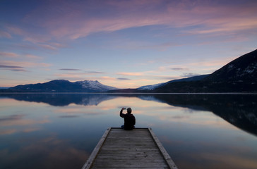 Snapping a photograph while enjoying the sunset colours over Shuswap Lake, in Sunnybrae, near Salmon Arm, British Columbia, Canada. MR102