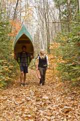 Young couple portage canoe  in northwestern end of Algonquin Park, Ontario, Canada.