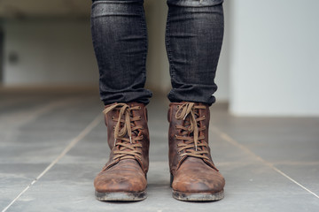 Close up view on man's legs in black jeans and brown leather boots.Toned picture.