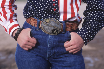 USA, cowgirl with USA shirt and champion belt buckle