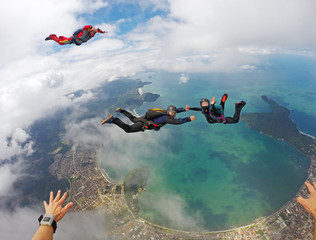 A happy group of skydivers above the beach