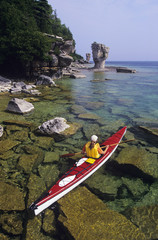 Young woman sea kayaking past Flowerpot Island, Fathom Five National Marine Park, Ontario, Canada.