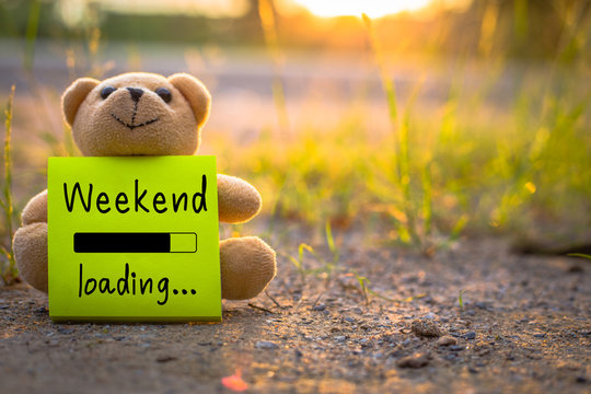 Happy Weekend on sticky note with teddy bear on nature background