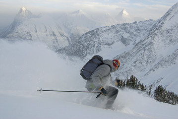 A male skier streaks down the slopes of Rogers Pass in front of MacDonald Peak and Mount Sir Donald, Selkirk Mountains, British Columbia